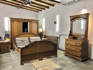 Dormitor cu dulap și comodă din lemn.