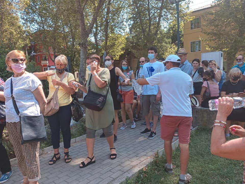 Italia: Voluntarii împart sticle cu apă alegătorilor care stau la coadă
