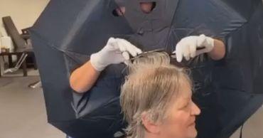 """В Нидерландах парикмахер работает в """"защитном костюме"""" из зонта."""