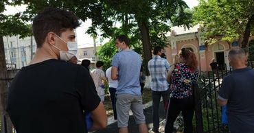 Люди стоят в очереди у наркодиспансера, чтобы оформить документы на водительские права. Фото: zdg.md