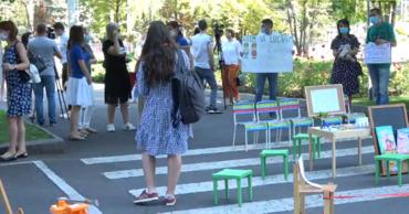 Участники митинга пришли протестовать с плакатами, игрушками, а также предметами детской мебели.