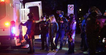В Портленде демонстранты сожгли флаг США и забросали полицейских банками и камнями.