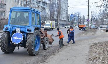 Муниципальные службы собирают песок с обочин дорог.