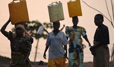 Женщины несут воду в канистрах в провинции Итури, Демократическая Республика Конго.