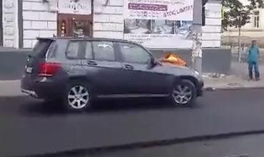 Рабочий, возмущенный действиями водителя, перекрыл дорогу и лег на капот автомобиля, не позволяя тому проехать.