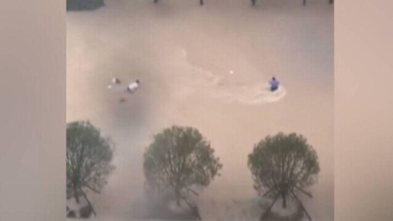 O femeie, filmată cum e luată pe sus de ape pe o stradă din China